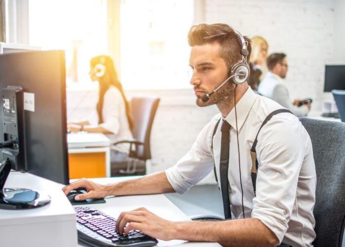 Technical support operator working on computer in call center